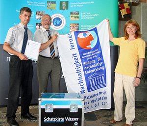 Regierungspräsident Dr. Paul Beinhofer, Leitender Regierungsdirektor Bertram Eidel und Dr. Anne-Kathrin Jackel mit der Fahne der UN-Dekade