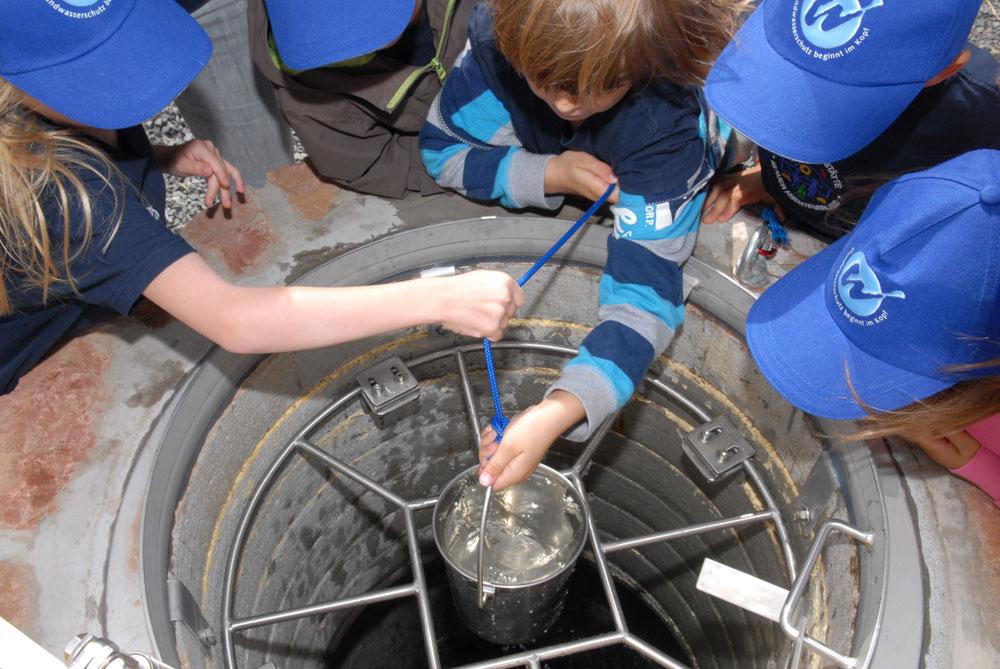 Kinder schöpfen Wasser aus dem Brunnen auf der Wasserinsel Alzenau