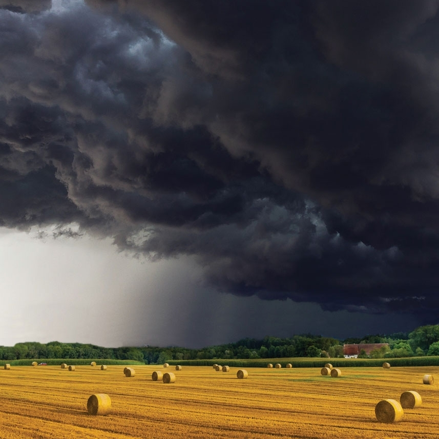 Gewitterwolken über abgeerntetem Weizenfeld