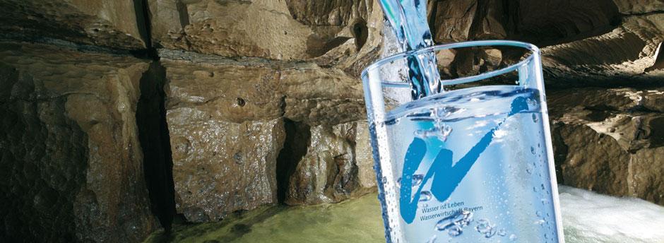 Teinkwasserglas vor einem Bild mit Grundwasser in eine Höhle