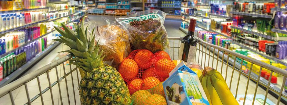 Lebensmittel im Einkaufswagen, der durch einen Supermarkt geschoben wird