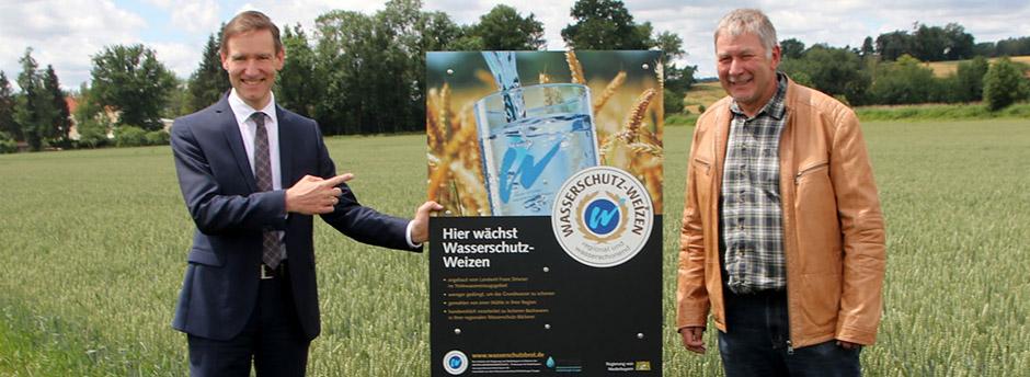 Regierungspräsident Rainer Haselbeck und Landwirt Franz Strixner im Weizenfeld neben einem Feldschild