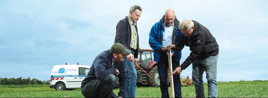 Wasserversorger und Landwirt bei einer Bodenuntersuchung
