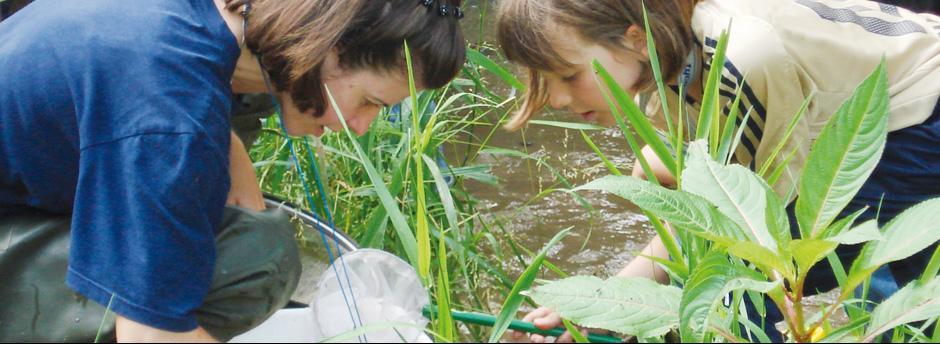 Kind und Lehrerin bei der Gewässeruntersuchung