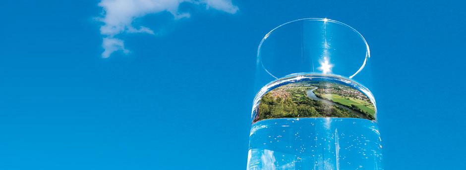 Titelmotiv der Aktion Grundwasserschutz. In einem Wasserglas vor blauem Himmel spiegelt sich eine unterfränkische Landschaft